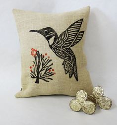 Hand Block Print Burlap Hummingbird Pillow. Hand Printed Burlap Pillow with Desert Landscape Hummingbird. Orange Floral Blossoms. The front of the pillow is constructed out of a soft burlap jute. At the center, there is a hand print of a hummingbird in black fabric ink with orange flower blossoms in fabric ink. The back is black and ivory ticking with a black exposed zipper. Since this print is hand printed, the print will vary slightly this adds to the character and uniqueness of the...