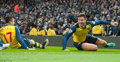 Giroud slides in jubilant celebration and is joined by Arsenal team-mate Alexis Sanchez as...
