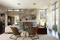 A rusticstone fireplace has an elegant contrast with the sleek…