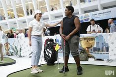 Former LPGA professional golfer Lorena Ochoa watches a fan putt on a putting green at a Presidents Cup fan zone in the Oculus Hub at the…