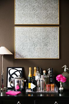 styling a bar, in a glass tray on a dark console, art above, chic and modern look with dark brown walls