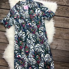 Lilly Pulitzer Apple Dress Tickle Me Fancy peacock Excellent condition Lilly Pulitzer Apple dress in Resort White Tickle Me Fancy peacock feather print. Size 0, collared with two breast pockets and tab sleeves. Cute pink buttons. Lilly Pulitzer Dresses Midi