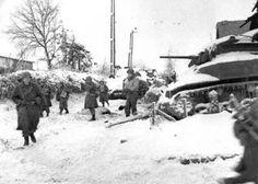Membres du 117ème Régiment d'infanterie, garde nationale de la Caroline du Nord, de la 30e Division d'infanterie, passer devant une M5 américain détruit « Stuart » réservoir sur leur marche pour capturer la ville de Saint-Vith à l'issue de la bataille des Ardennes. St. Vith a été en grande partie détruite pendant la bataille de terrain et attaque aérienne ultérieures. Les forces américaines ont repris la ville le 23 janvier 1945