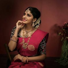 In a bridal look in a pink color saree, elbow length sleeve blouse design, necklace, long chain, head piece / maang tikka and gold jewelry South Indian Bride Saree, Kerala Wedding Saree, Kerala Bride, Indian Silk Sarees, Bridal Hairstyle Indian Wedding, Indian Bridal Outfits, Indian Bridal Fashion, Silk Saree Blouse Designs, Bridal Blouse Designs