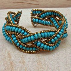 This intricate turquoise bracelet is made of wooden beads with strands of golden glass beads surrounding each length of the wooden beads. The
