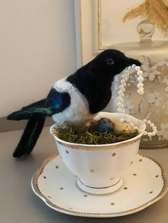 Hand made, 100% woo, needle felted magpie, nesting in a vintage style china teacup and saucer, and surrounded by her stolen treasures. The magpie is made from black and white 100% wool, with green, purple and blue wool highlights on her wings and tail. Bird measures approx. 10 in. from