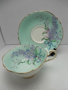 turquois cup and saucer with possible a wisteria or lilac flower