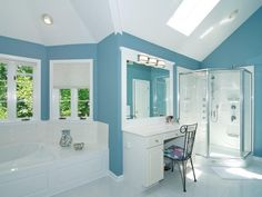 Bright blue walls create amazing contrast against the white in this bathroom. Lots of windows and a skylight ensure that plenty of light comes into the room. The vanity chair brings in a subtle touch of color with its floral cushion.