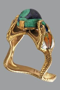 Symbolist Serpent Ring, CHARLES BOUTET DE MONVEL (1855-1913). The Hooded Cobras clutching a blue green cabochon 'world', gold, enamel, lapis and malachite. Marks: Signed 'B. de Monvel', French, c.1900.