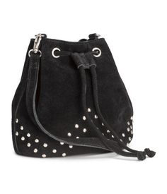 PREMIUM QUALITY. Small drawstring shoulder bag in suede with studs at front. Detachable, adjustable shoulder strap and one inner compartment. Lined. Size 4 1/4 x 6 3/4 x 7 1/4 in.