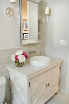 Soft gray walls, marble flooring and a furniture-style vanity create an elegant spot for guests to freshen up. Heather Scott Home & Design removes the wall-mounted cabinet above the toilet, making the space feel much larger and brighter.