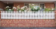 white picket fence red brick