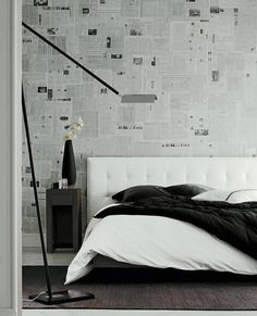 Nador bed by Ligne Roset, drawing  inspiration from the high-end hotel market, the bed and headboard were designed to inspire a sentiment of generous comfort and welcoming softness. Old newspapers attached to the wall like wallpaper help add depth to the black and white colour palette. #Bedroom