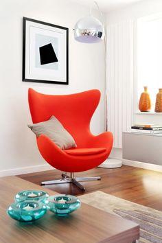 lampadaire arc métallique et fauteuil Oeuf Jacobsen en rouge orangé dans le salon blanc