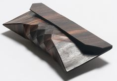 Artisanal Wood Clutch from Tesler + Mendelovitch. Constructed from 100% wood, 100% hide. The geometric surface design provides necessary flexibility, the wood texture is soft to the touch, and both are delicate and wear resilient. It has a leather lining and magnetic closure. Made from Ebony, a rare and valuable wood derived from a tree that can take over 100 years to mature. The tight grain can be polished to a marble-like smoothness. Each bag features a different wood grain, no two are…