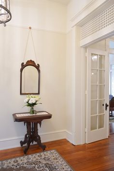 Entryway, foyer vintage antique table and mirror - Morgan Ford Southern Romance House in Mobile, Alabama - Renovation by Phantom Screens