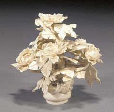 A Chinese ivory flower carving 20th Century carved in the form of a peony plant issuing from a censer decorated with a coiled dragon. Christie's.