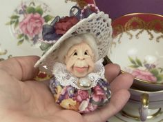 Little Old Lady YoYo Doll, wearing a crocheted hat with flowers. and a lace collar.