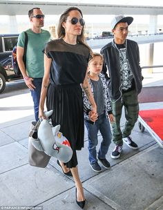 Three's a crowd: The 41-year-old actress was not alone at the international airport and travel hub as she was joined by two of her sons including Maddox, 14, and seven-year-old Knox