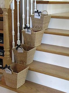 Each family member has a basket with their name on it....he/she is then responsible for carrying it up the stairs. Great idea to organize each kid's stuff!