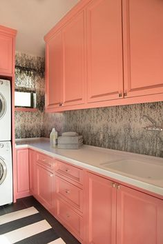 Chic laundry room features coral pink cabinets paired with white ocuntertops and a wallpapered backsplash.