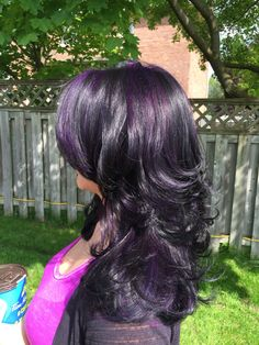 Black with bright purple highlights. Square layers on natural curly hair blow dried straight with a curl on the ends