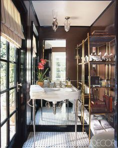 CHOOSE METALLIC PIECES TO BRING OUT MORE SHINE  A mirrored wall and a brass-and-marble étagère add an urbane touch to the powder room of Mik...