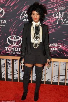 Edgy chic:Janelle Monae paired her little black skirt with a white collared blouse, jacket and tall boots