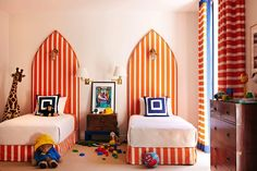 Super cute blue and orange boys' bedroom with tall twin headboards upholstered in white