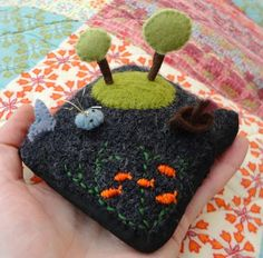 A pin cushion sea-scape.  Of course! The boat and fish are attached to pins so they can be taken out and moved about.