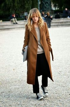 Midi overcoat in cognac, featuring a notched collar, slash pockets and a tie belt, hanging. Worn over a taupe sweater, black demi flare cropped jeans and Converse. She is carrying an oversized envelope clutch in gray. Statement earrings. A touch of grunge, which is always nice. Style Planet