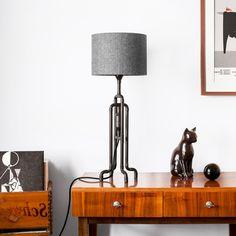 Unusual table lamp in black patina metal finish. Here with custom herringbone tweed shade on mid-century modern console table.