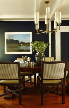 A modern dining room is given a dramatic edge with navy walls.