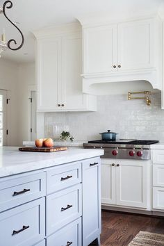 Stunning white and blue kitchen boasts a kitchen hood concealed by white shaker cabinets and mounted above a Wolf integrated cooktop fixed against white glazed subway backsplash tiles and below an antique brass swing arm pot filler.