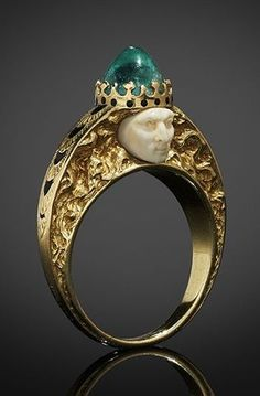 Lalique Ring: yellow gold, each side centered by a carved ivory face, the ring is surmounted by a cabochon emerald, the setting of the stone formed & enamelled to resemble a crown, the subject's hair sensously tumbles down the deeply engraved shoulders, the top of the shoulders are decorated w/overlapping engraved leaves filled w/black enamel: signed 'LALIQUE'