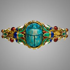 An antique gold and enamel scarab bracelet in the Egyptian Revival style with multicolored enamel lotus leaves centering on a blue faience scarab, in 18k. Marcus & Co. United States.