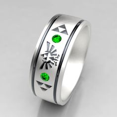 A tribute to Legend of Zelda in a unique mens wedding band! This ring comes with 2 Chatham lab created emeralds for nice accent stones. Also available with lab created rubies, or sapphires upon request. This 7mm wide wedding band is made from recycled silver and is handmade with a comfort fit to your size. The ring is carved from wax, then cast in the metal. From there it is finished by hand to achieve a great wearable look. Ring Specs: ● 7mm width ● 1.5mm Thickness- good weight, sturdy…