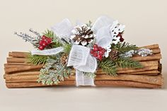"12""L Cinnamon Bundle with Pine, Red Berries, White Tipped Pine Cone, a sparkled snowflake and a White Bow, Snowy Christmas Collection"