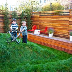 Landscape design, grass, bumps for kids to run up and down, outdoor dining, wood stained fence. Wood bench, privacy plantings.