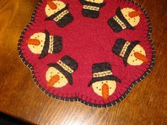 "This mat is great for the winter months. It is a snowman head with a top hat. It is 9"" in dia, with a red back ground attached to a black backing with a blanket stitch. All my mats are hand cut and ha"