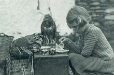"""This photo from a 1938 issue of National Geographic captioned, """"Anne and her family lived alone on an island. She enjoyed having tea time with her friends the spiny lobster and baby hawk."""""""