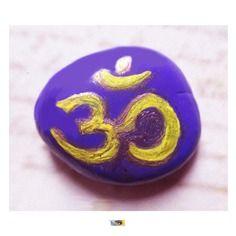 """Médaillon galet peint main """"om"""" sur fond violet couleur jaune et or, symbole hindouisme"""