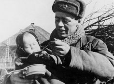 Russian soldier feeding a child in a village liberated from Nazi rule.
