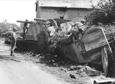 Four GIs inspect German armored vehicles neutralized on the side of a road. In the foreground lies a dead German soldier & another between the two Wespes. The US soldier on the left is Brig. Gen. Isaac D. White, CCB commander, of the 2nd AD Div. The soldier on the right is climbing on an overturned halftrack. July 31, 1944.