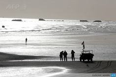 FRANCE, Arromanches-les-Bains : Men dressed in vintage World War II US military uniforms stand next to a Willis jeep, on the beach, in the morning in Arromanches, western France, on June 5, 2014, a day before the start of the D-Day commemorations. AFP PHOTO / LUDOVIC MARIN
