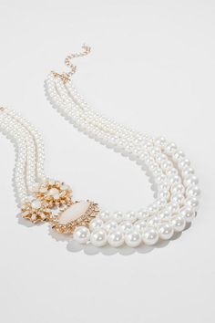 """The Blair Pearl Strand Necklace adds a classy touch to any look. Three strands of varying size pearls are adorned with golden brooches accented with crystal rhinestones & ivory gems. Wear this with a little black dress & have an Audrey moment!<br /> <br /> - Finished with a lobster claw clasp<br /> - 21"""" length<br /> - 3.5"""" extension<br /> - Lead & nickel free<br /> - Imported"""