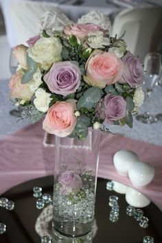 Mixed ball arrangement of pink, white and lilac roses with penny gum, mini carnations, million star and penny gum
