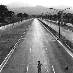 """Un solitario atleta corre por el despoblado Periférico en 1968. A la derecha se ve la escultura 17 de la Ruta de la Amistad, creada por el marroquí Mohamed Melehi y situada en el rumbo de Villa Coapa.    Crédito imagen: """"Historia gráfica de la Ciudad de México"""" - México 68."""