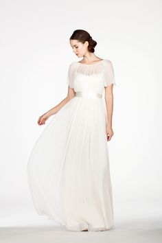 RC6257 l A sheer illusion dress with hand beaded flutter sleeves that drape and frame perfectly around the shoulders. This vintage-inspired dress showcases the collarbones and neckline of the bride beautifully.