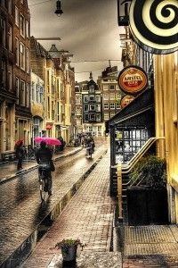 Amsterdam - Biking with pink umbrella